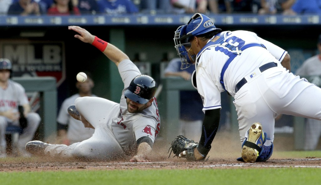 Mitch Moreland of the Red Sox beats a tag by Kansas City catcher Salvador Perez to score on a three-run double by Xander Bogaerts in the fifth inning of Boston's 15-4 win Saturday night.