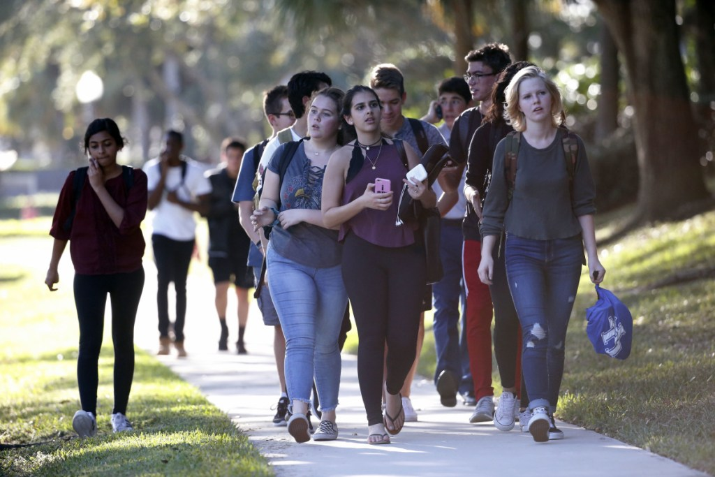 Groups of students leave Marjory Stoneman Douglas High School in Parkland, Fla. Pinellas County Sheriff Bob Gualtieri said the suspect in the shooting's mother let him buy a gun.