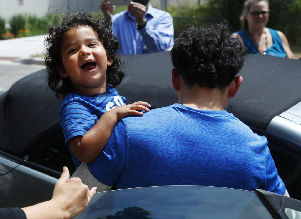 Ever Reyes Mejia, of Honduras, carries his son to a vehicle after being reunited and released by United States Immigration and Customs Enforcement in Grand Rapids, Mich., on Tuesday. Two boys and a girl who had been in temporary foster care in Grand Rapids were reunited with their Honduran fathers after they were separated at the U.S.-Mexico border about three months ago.