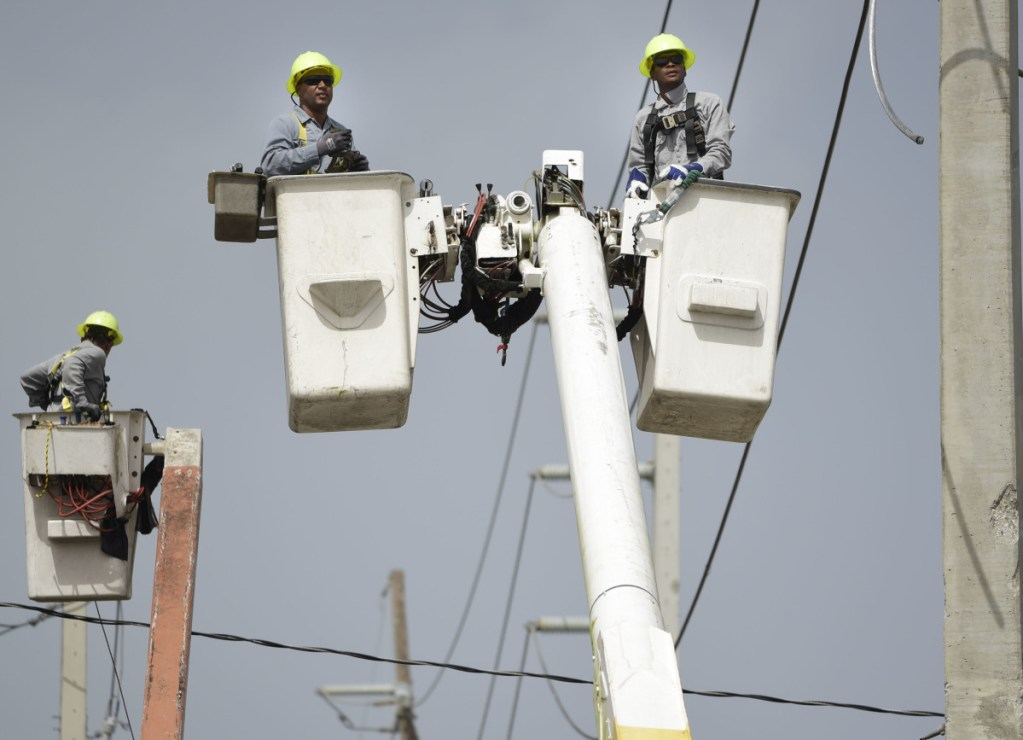 Workers patch up damaged distribution lines last October after Hurricane Maria hit Puerto Rico, causing widespread damage. As another hurricane season approaches, officials are still struggling to finish the work.