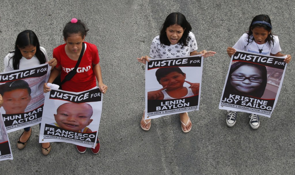 Protesters hold posters of young victims who died under President Rodrigo Duterte's so-called war on drugs during a rally coinciding with his third State of the Nation Address Monday, July 23, 2018, in Quezon city, northeast of Manila, Philippines. The protesters assailed Duterte for allegedly failing in his promises to alleviate poverty as well as his so-called war on drugs which saw the killings of thousands, mostly the poor. (AP Photo/Bullit Marquez)