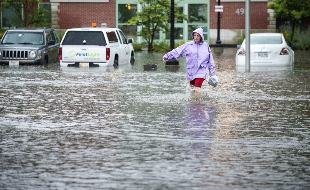 Jessica Morgan sloshes down Maple Street in Lewiston as she makes her way to work Thursday afternoon during a downpour that flooded streets, businesses and houses throughout the area, which received more than an inch of rain in less than two hours.