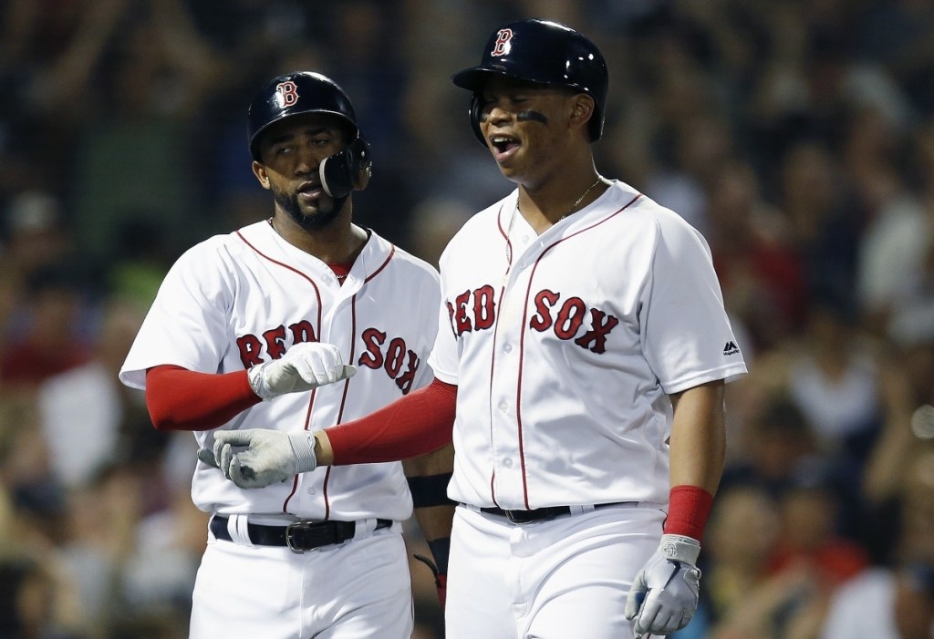 Rafael Devers, right, and Eduardo Nunez celebrate after scoring on a triple by Jackie Bradley Jr. in the fourth inning Saturday night against the Minnesota Twins. The Red Sox overcame a 4-1 deficit and pulled away late for a 10-4 victory. (Associated Press/Michael Dwyer)
