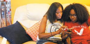 JENNEA BIVENS, left, talks with her 13-year-old daughter, Ayrial Miller, about the contacts in her Snapchat social media account while sitting on the couch in their Chicago apartment in June. Bivens uses a monitoring app to track and limit her daughter's phone use, but says there's no replacement for a face-toface conversation, especially about social media. THE ASSOCIATED PRESS