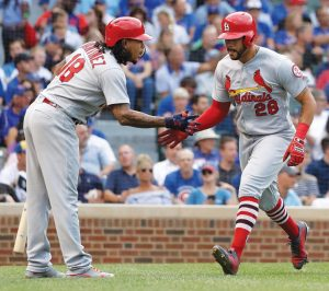 ST. LOUIS CARDINALS hitter Tommy Pham (28) celebrates his home run off Chicago Cubs starting pitcher Kyle Hendricks with Carlos Martinez during the second inning of a baseball game on Thursday in Chicago. The Cubs began the second part of the season with a 9-6 victory. THE ASSOCIATED PRESS