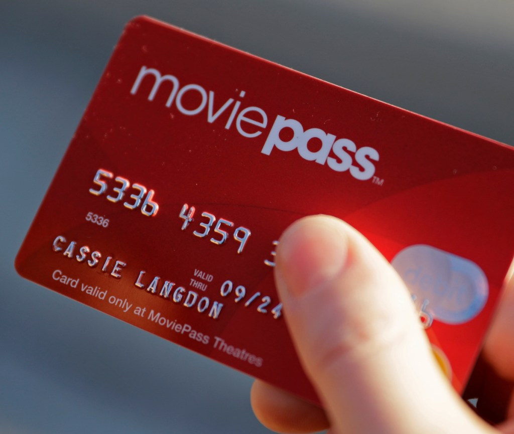 FILE - In this Jan. 30, 2018, file photo, Cassie Langdon holds her MoviePass card outside AMC Indianapolis 17 theatre in Indianapolis. MoviePass, the discount service for movie tickets, is raising prices by 50 percent and barring viewings of most major releases during the first two weeks. (Associated Press)