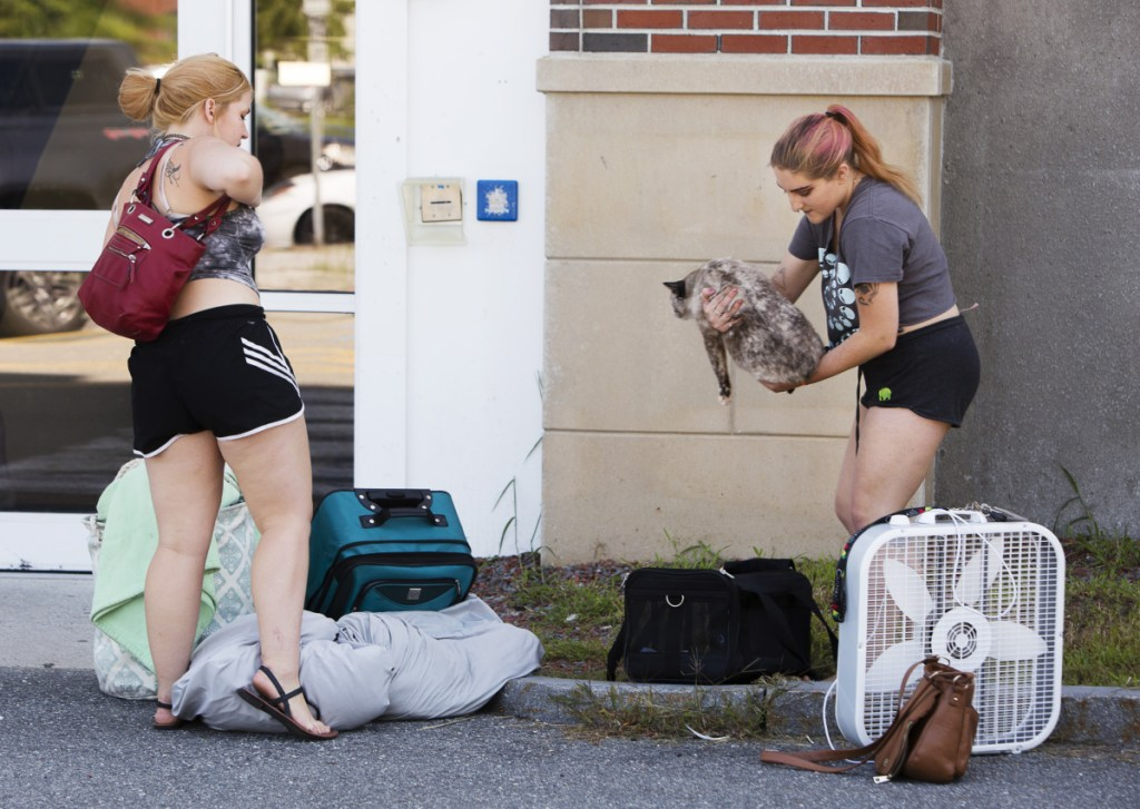 Southern Maine Community College sophomores Olivia Treadwell and Lauryn O'Connor wait for a ride to transport their belongings away from the Spring Point Residence Hall on Sunday because of a mold infestation.
