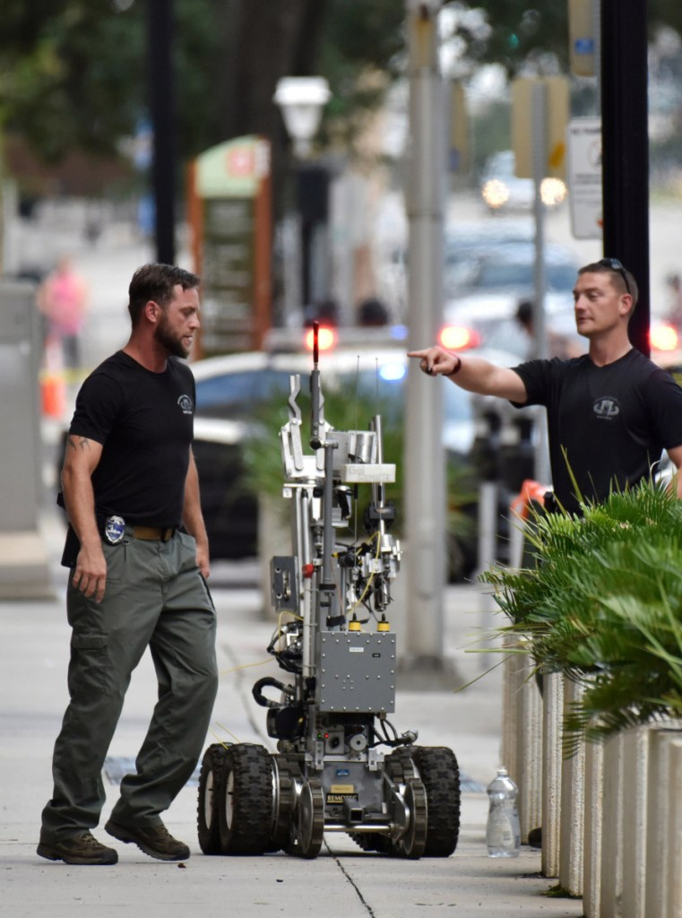 Bomb squad police prepare a robot to enter a parking garage a block away from the scene of a multiple shooting in Jacksonville.