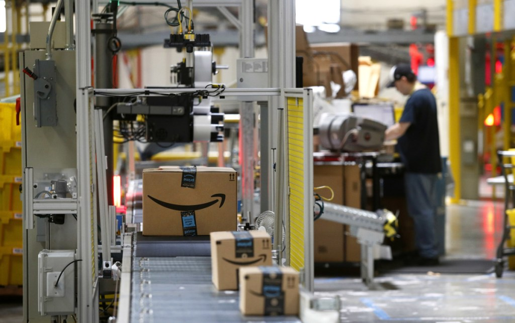 "A machine scans packages at an Amazon fulfillment center in Baltimore. Amazon is paying workers to defend the company on Twitter, reassuring critics that they make a living wage and are allowed to take bathroom breaks. One worker tweeted: ""We are totally happy working for an amazing company."""