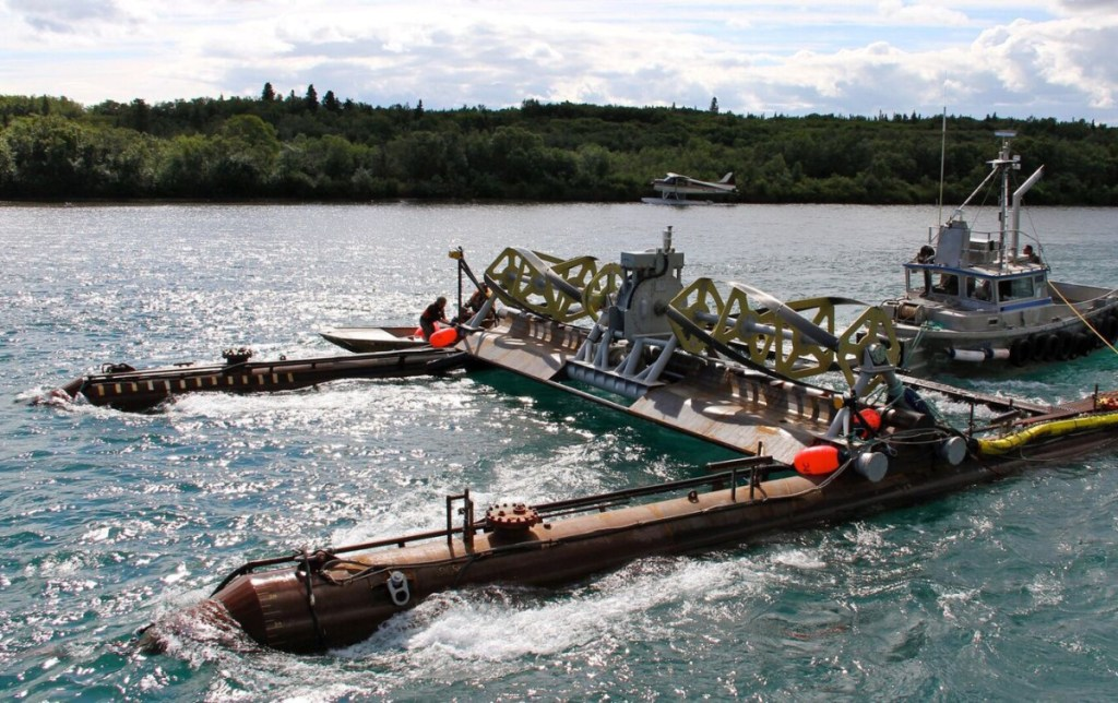 A tugboat maneuvers Ocean Renewable Power Co.'s RivGen Power System into place on the Kvichak River in Alaska. Over a two-year trial, the system provided about a third of the power for a remote village nearby.