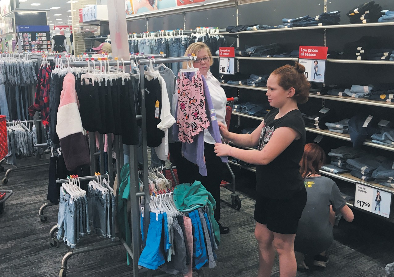 SALVATION ARMY LT. KIRSTEN CHILDS assists two girls with their back-to-school shopping on Wednesday at Target in Topsham. The Salvation Army teamed up with Target to help kids purchase needed supplies for the upcoming year. CHRIS QUATTRUCCI / THE TIMES RECORD