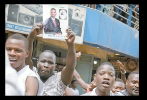 SUPPORTERS of pop starturned lawmaker Kyagulanyi Ssentamu, also known as Bobi Wine, hold a poster of him as they gather in the Kisekka Market area of Kampala, Uganda, today. AP PHOTO /RONALD KABUUBI