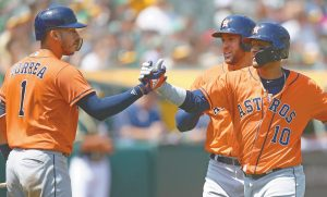 HOUSTON ASTROS Yuli Gurriel, right, celebrates with Carlos Correa (1) after hitting a three-run home run off Oakland Athletics' Sean Manaea in the third inning of a baseball game Sunday. The Astros avoided a sweep to the A's with a 9-4 victory. THE ASSOCIATED PRESS