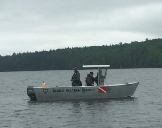 A Maine Warden Service dive boat pulls divers underwater in Moosehead Lake while searching for a missing man Saturday.