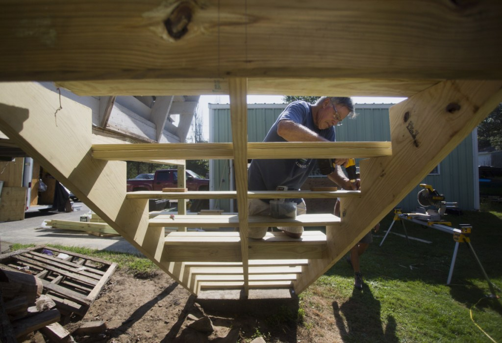 John Lichter, a volunteer with Harpswell Aging at Home, installs exterior stairs at the home of Steve Taylor, 83, on Aug. 29. In recent years, more than 100 Maine communities have established Aging in Place initiatives to cover what they see as a state remiss to live up to its responsibilities.