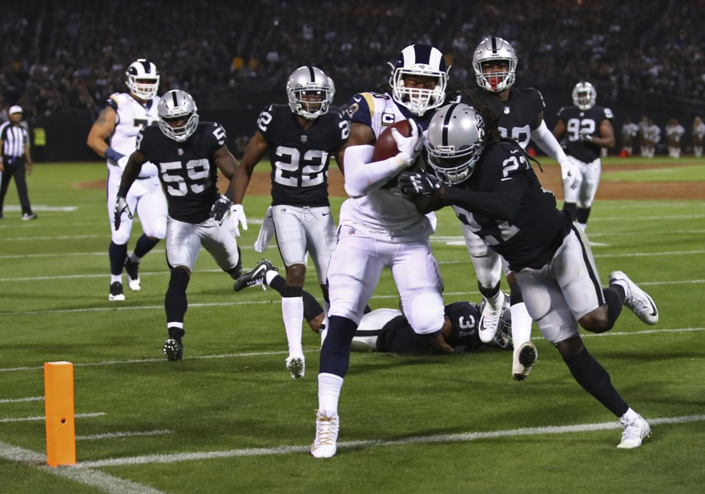 Los Angeles running back Todd Gurley carries the ball over the goal line for a touchdown as Oakland defensive back Reggie Nelson tries to make the tackle Monday night.