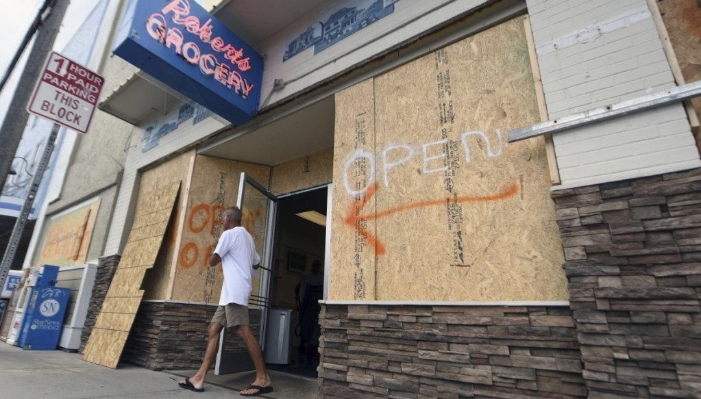A man leaves the boarded-up Robert's Grocery in Wrightsville Beach, N.C., on Tuesday. Across the Carolinas, Virginia and Georgia, businesses are bracing for Hurricane Florence
