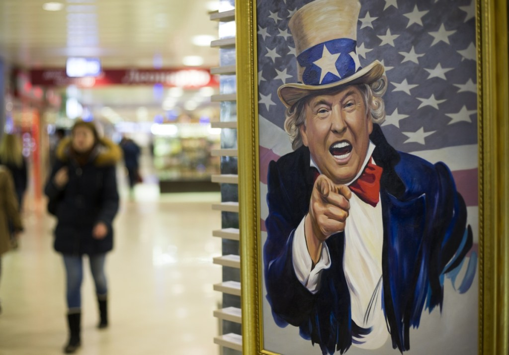 People walk past a caricature picture of President Trump on sale in a shopping mall in Moscow.  Trump's executive order authorizing sanctions on foreigners who mess with American elections could herald new headaches for Russia.