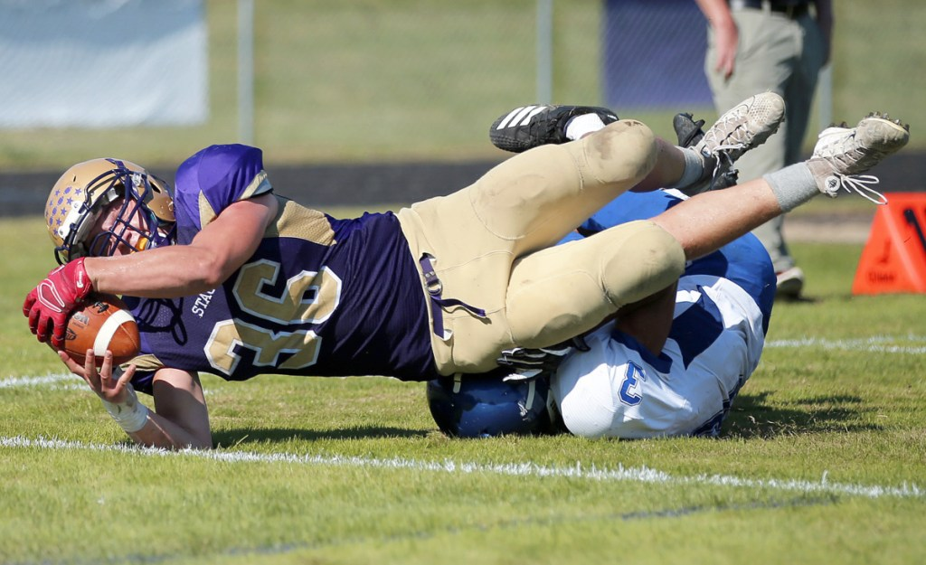 Teigan Lindstedt of Cheverus stretches for the end zone while being tackled by Lewiston's Dylon Jackson as he scores the winning touchdown Saturday in a 19-13 victory at Boulos Stadium.