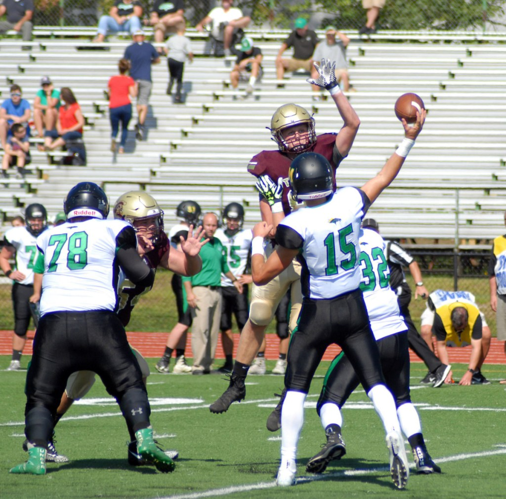 Thornton Academy's Ethan Logan tries to knock down a pass from Nick Roberge of Massabesic during Thornton Academy's 63-7 win Saturday in Saco.
