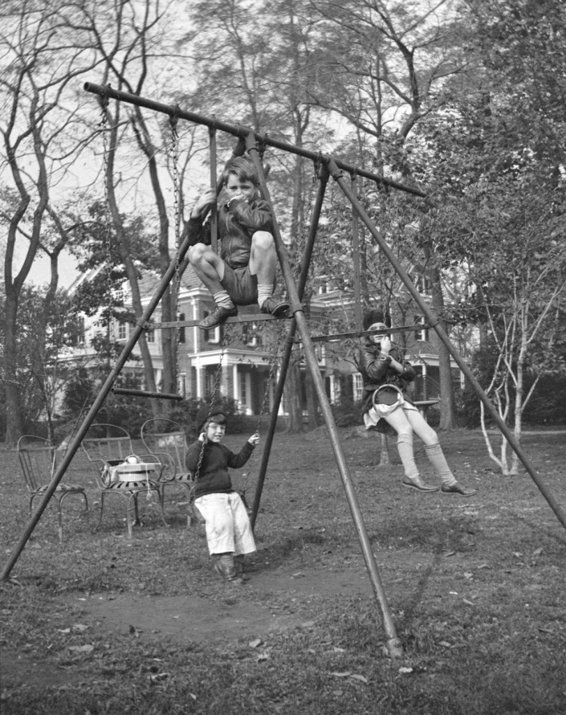 In this October 1934 photo, Robert F. Kennedy, top front, Edward M. Kennedy, left rear, and Jean Kennedy, right rear, play on a swing set in Bronxville, N.Y.