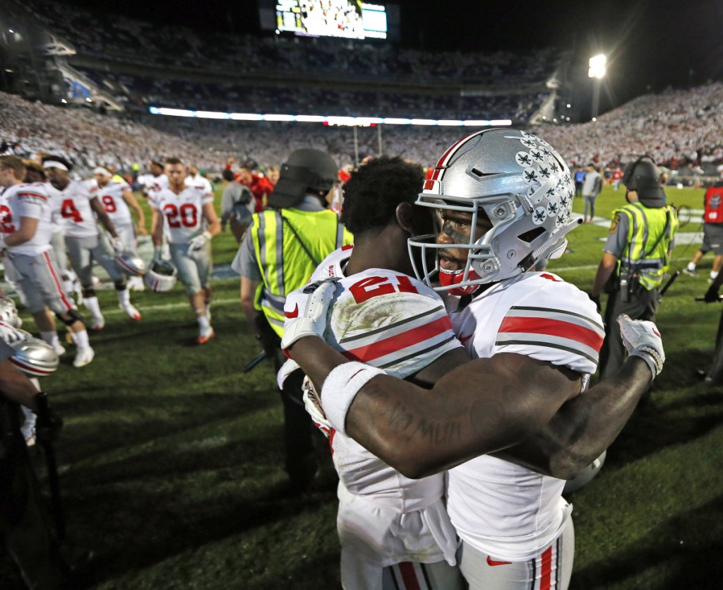 Ohio State's Paris Campbell and Johnnie Dixon (1) embrace after beating Penn State 27-26 in State College, Pa. on Saturday.