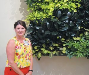 "MELISSA CACCAMO, director of ambulatory services, stands in front of the ""living wall"" in the Topsham Care Center's atrium. CHRIS QUATTRUCCI / THE TIMES RECORD"