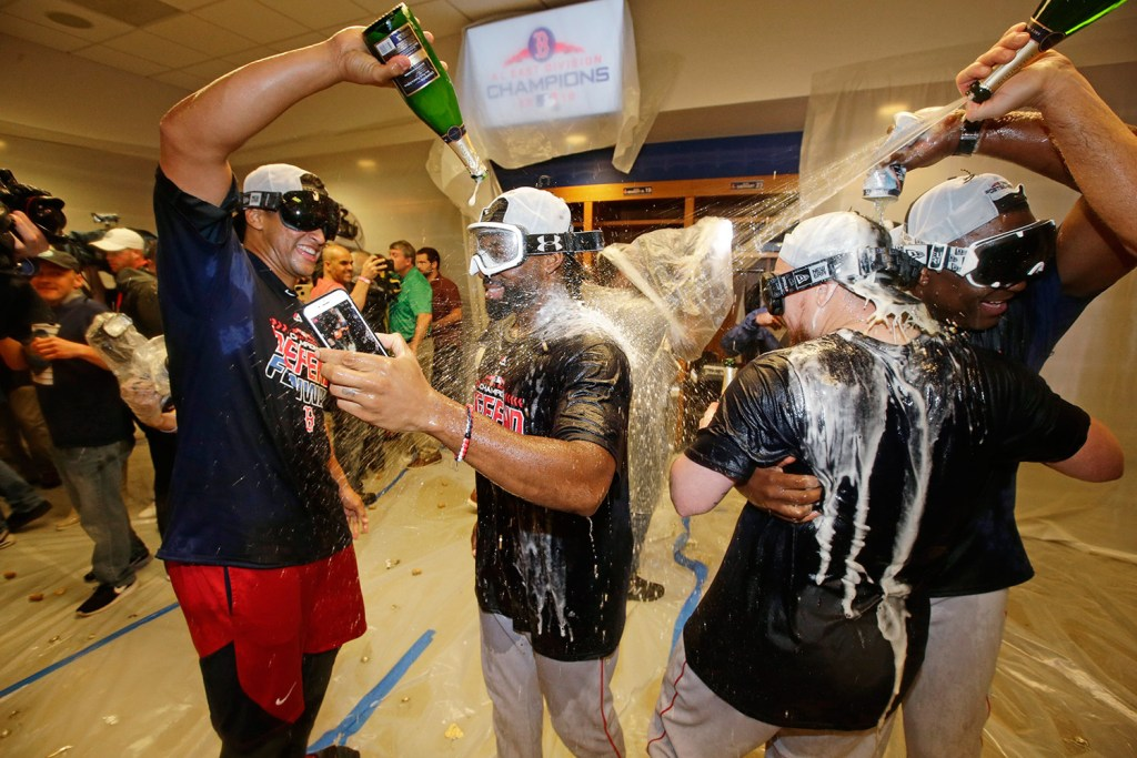 Jackie Bradley Jr., center, William Cuevas, left, and Christian Vazquez, second from right, celebrate after the Red Sox clinched the AL East title with an 11-6 win over the New York Yankees on Thursday night.