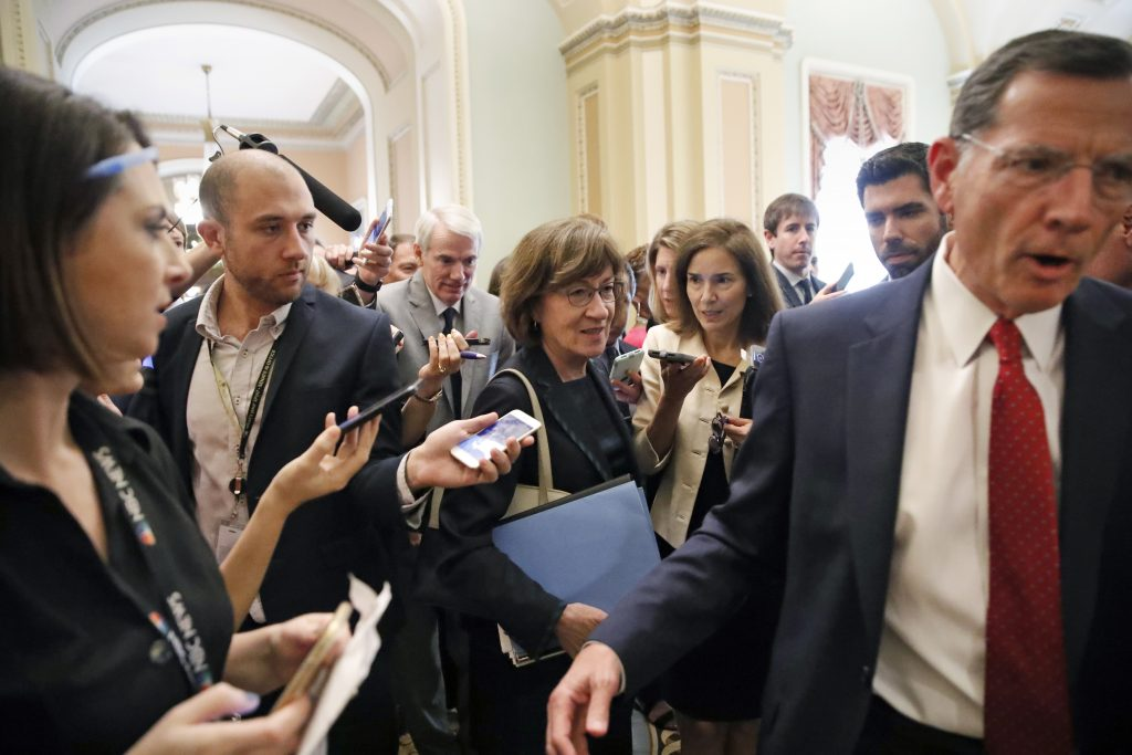 Sen. John Barrasso, R-Wyo., right, leads Sen. Susan Collins, R-Maine, followed by Sen. Rob Portman, R-Ohio, through a crowd of reporters after a Republican lunch meeting on Capitol Hill last week.