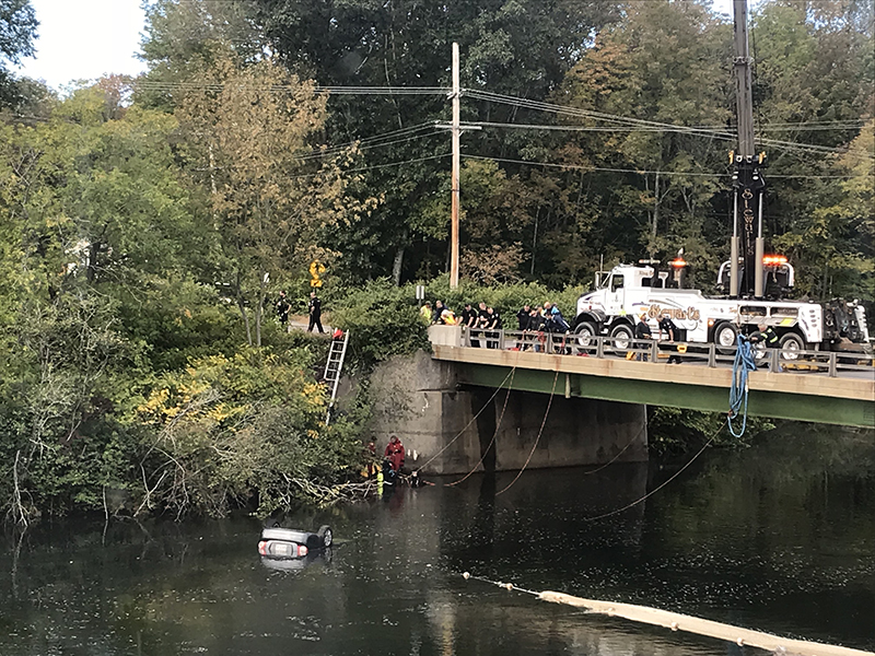 Officials at the Presumpscot River where a car was found floating Thursday morning.