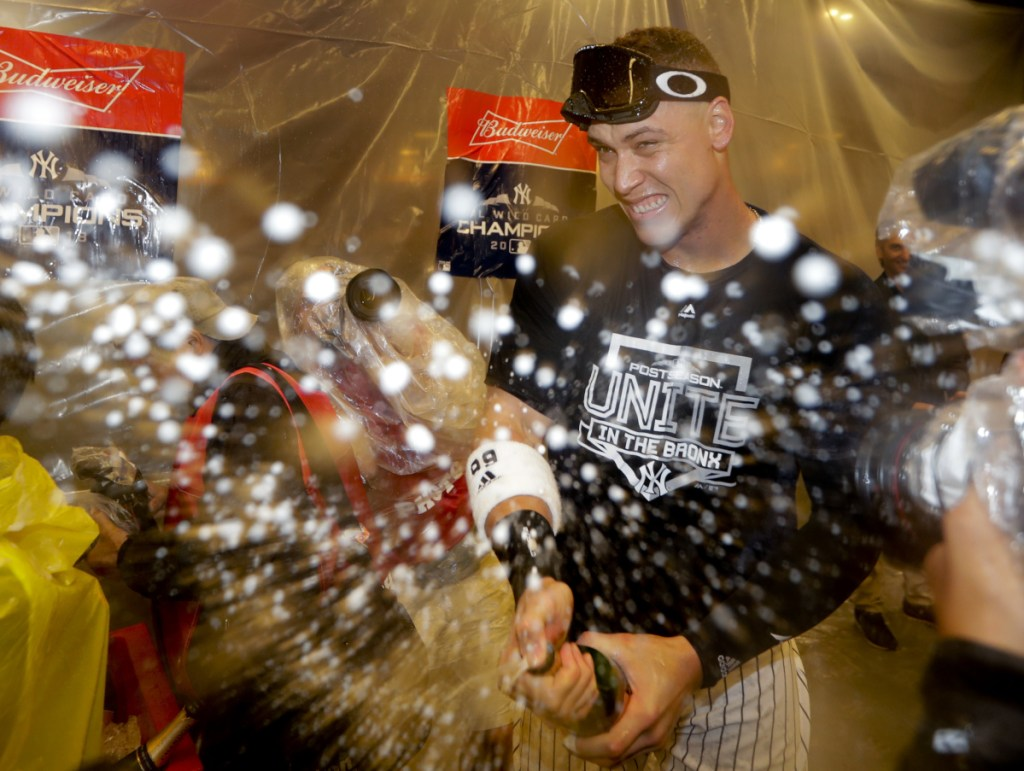 Aaron Judge celebrates in the locker room after the New York Yankees beat the Oakland Athletics, 7-2, in the American League wild card game on Wednesday night in New York.