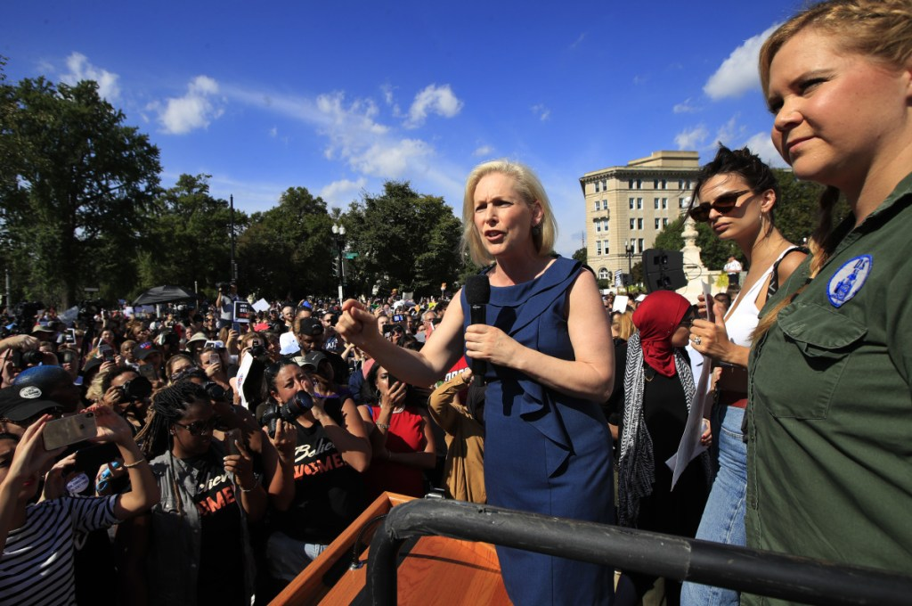 Sen. Kirsten Gillibrand, D-N.Y., with actress and comedian Amy Schumer, right, and actress model Emily Ratajkowski, center, speaks at a rally against Supreme Court nominee Brett Kavanaugh at the Supreme Court in Washington on Thursday.