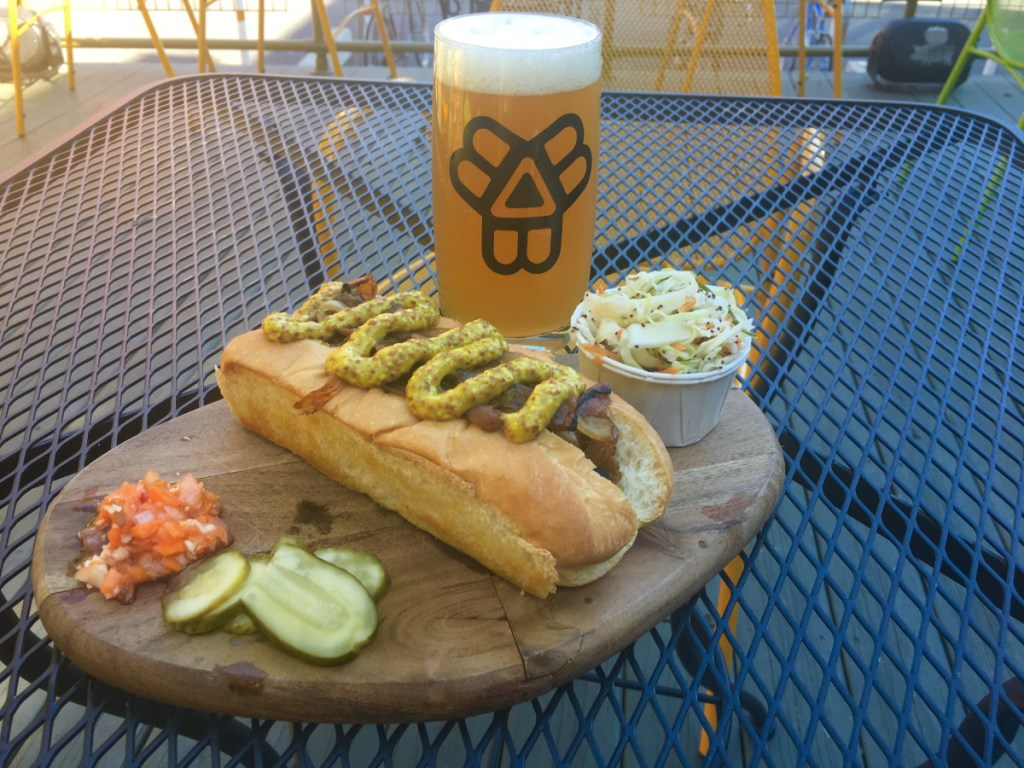 The vegan sausage at The Thirsty Pig comes covered in caramelized onions and spicy brown mustard. It is accompanied by vinegar coleslaw, Morse's Sauerkraut pickles and housemade hot carrot relish.