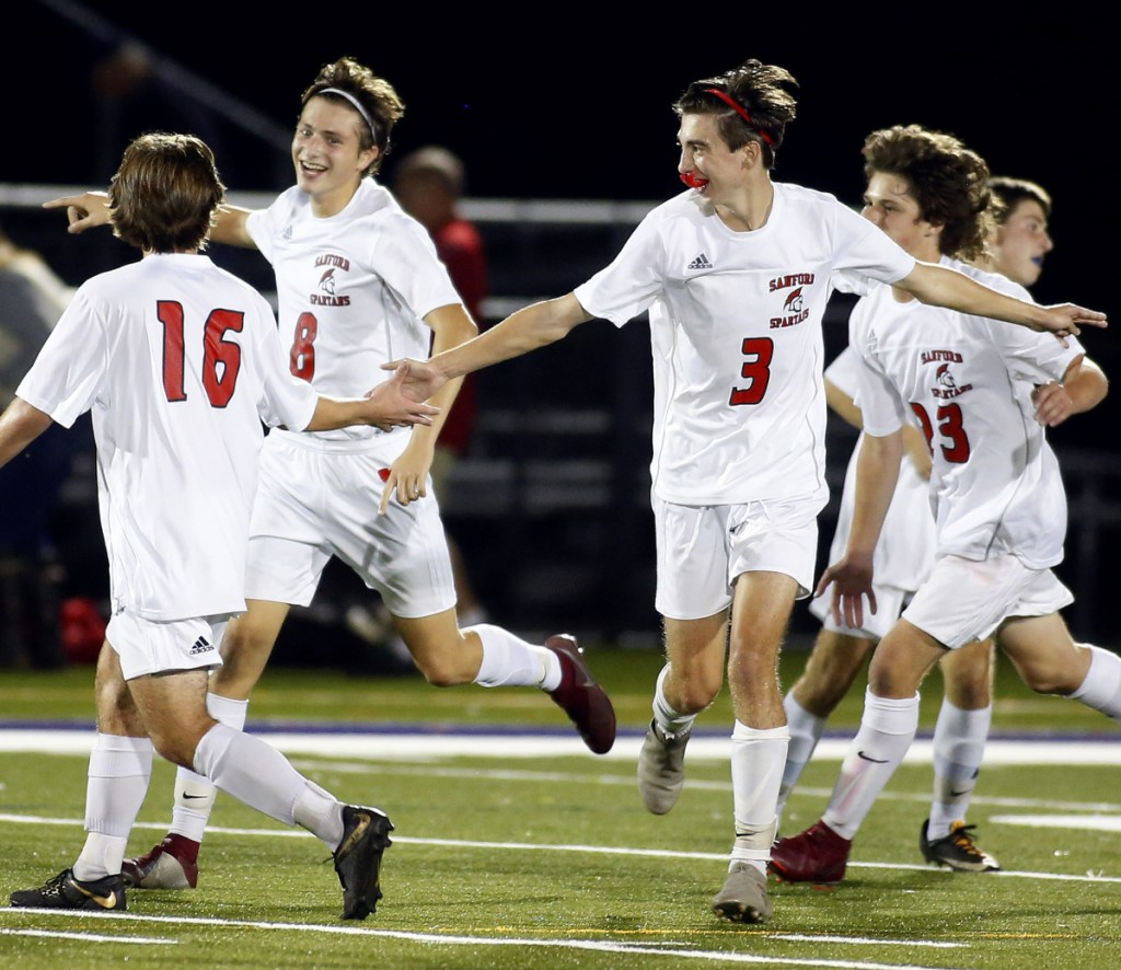 Sanford players celebrate their second goal, scored by Alex Kirven, second from left, in the second half of Tuesday's win.