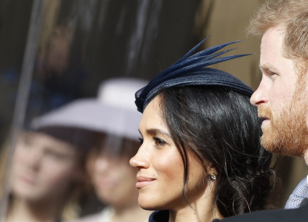 Prince Harry and his wife Meghan, Duchess of Sussex, smile as they wait for the bridal procession at the wedding of Princess Eugenie of York and Jack Brooksbank in St George's Chapel, Windsor Castle, near London, England on Oct. 12, 2018.