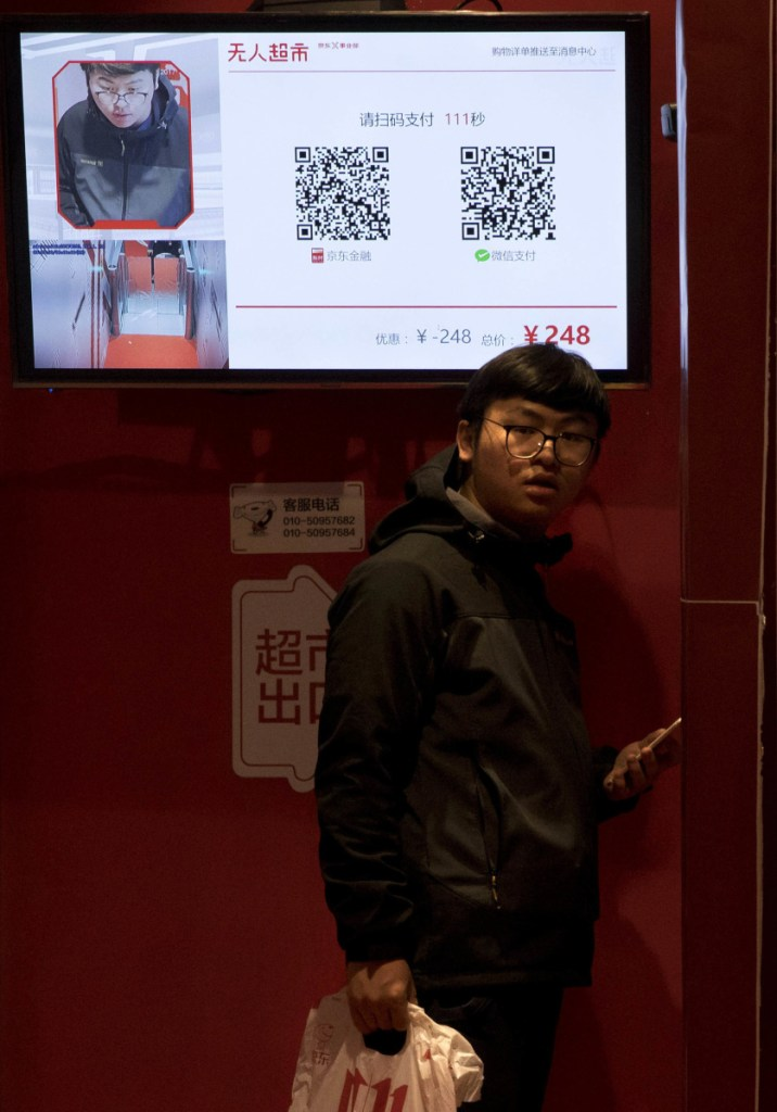 A shopper waits to leave an unstaffed convenience store in Beijing that uses facial recognition to take payments.
