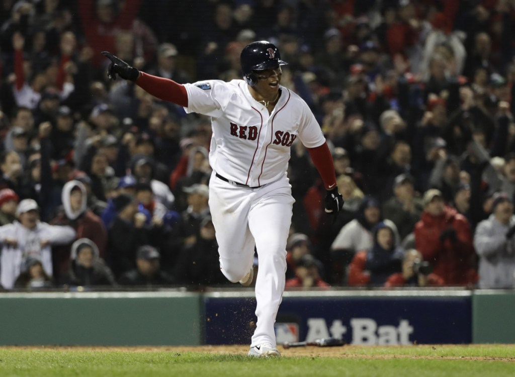 Rafael Devers of the Red Sox hits an RBI single to score Andrew Benintendi in the fifth inning of Game 1 of the World Series Tuesday night in Boston.