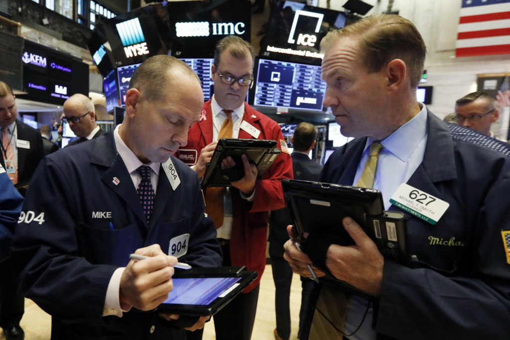 """Michael Urkonis, from left, William Lawrence and Michael Smyth work at the New York Stock Exchange on Monday. """"Investors are on pins and needles,"""" said a Wells Fargo Private Bank official."""