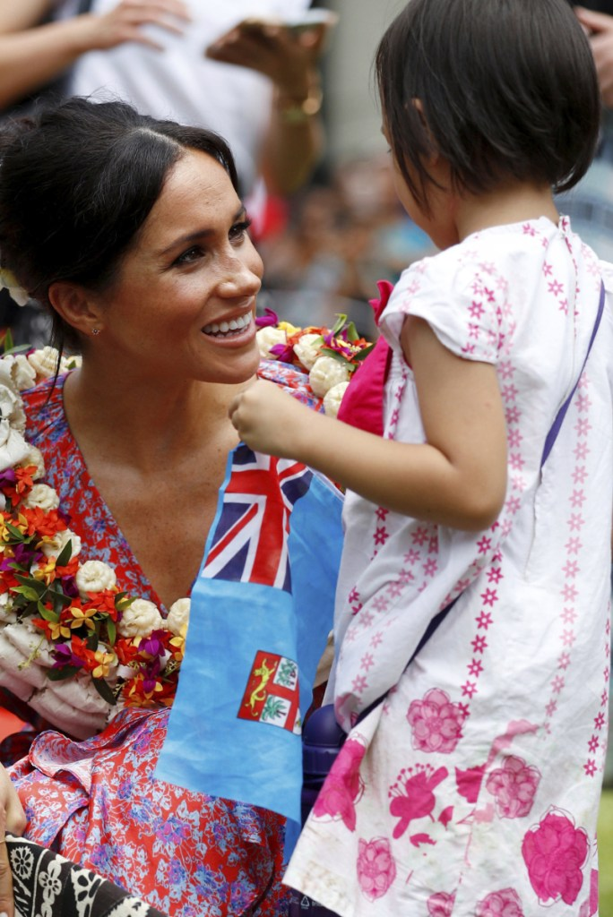 The duchess of Sussex greets Natasha Manuela, 3, in Suva, Fiji, on Wednesday.