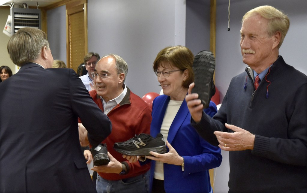 U.S. Sen. Angus King, I-Maine, right, holds up a New Balance athletic shoe as Dave Wheeler, left, of the company hands U.S. Sen. Susan Collins, R-Maine, and U.S. Rep. Bruce Poliquin, R-2nd District, a sample shoe on Tuesday in Norridgewock.