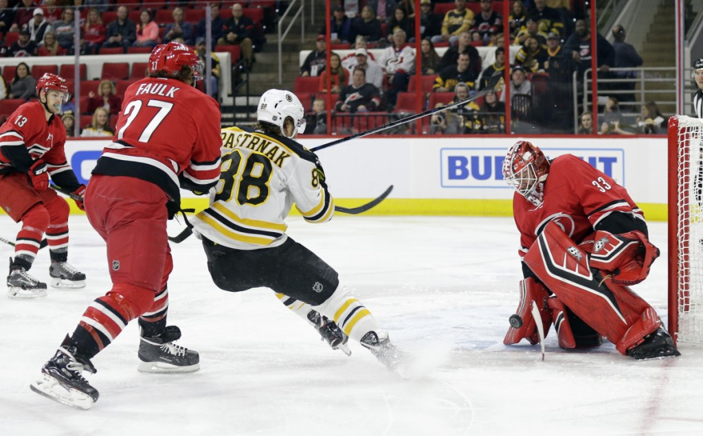 Carolina's goalie Scott Darling, a former UMaine goalie, blocks the net while Justin Faulk defends against Boston's David Pastrnak in the first period Tuesday night at Raleigh, N.C.