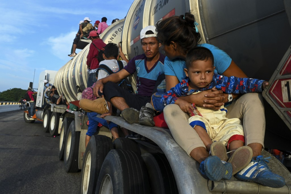 Some of the thousands of migrants traveling in a caravan toward the U.S. border, including Miguel de Jesus, 4, catch a ride atop a truck on a highway in Santiago Niltepic, Mexico, on Tuesday.  (Washington Post/Carolyn Van Houten)
