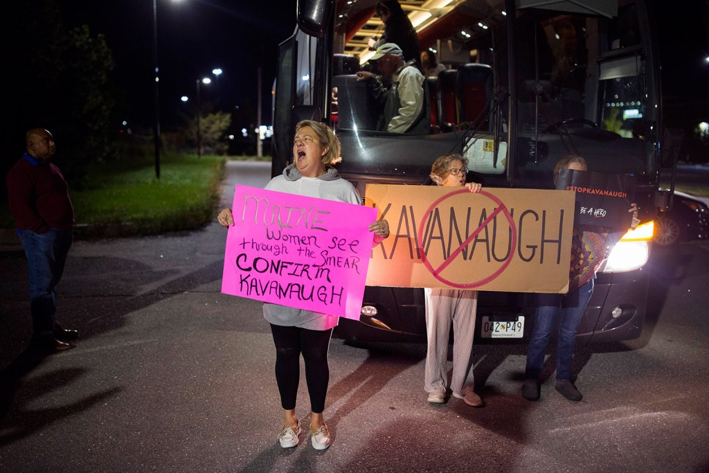 Susan Melcher of Pownal protests in front of the charter bus bound for Washington, D.C., from Portland on Wednesday night. The Mainers who left Portland, including Susan Feiner, holding an anti-Kavanaugh sign at center, hope to meet with Sen. Susan Collins to voice their concerns about Supreme Court nominee Brett Kavanaugh. Melcher, who supports Kavanaugh, said she decided to voice her opinion to stand up for Kavanaugh and his family.