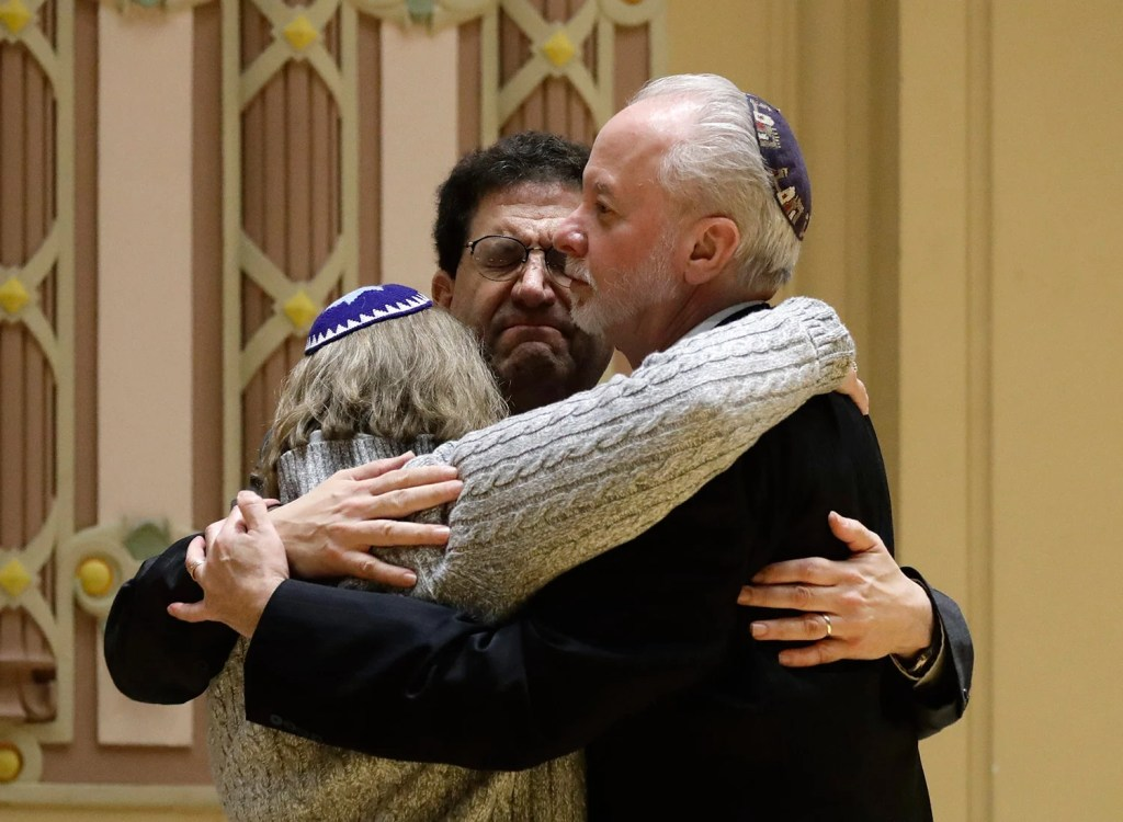 Rabbi Jeffrey Myers, right, of Tree of Life/Or L'Simcha Congregation hugs Rabbi Cheryl Klein, left, of Dor Hadash Congregation and Rabbi Jonathan Perlman during a community gathering held in the aftermath of the deadly shooting in October.