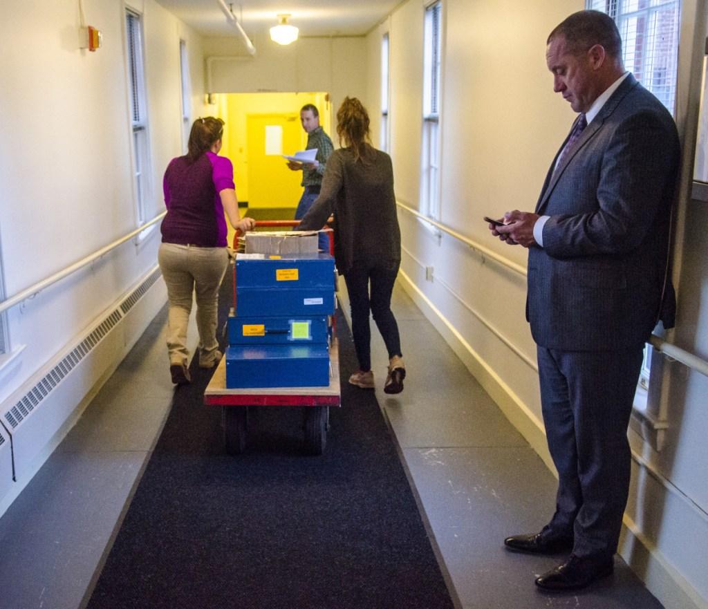 Josh Tardy, attorney for the Bruce Poliquin campaign, right, observes the chain of custody as Department of the Secretary of State staffers move ballots Thursday afternoon in the Elkins Building in Augusta.