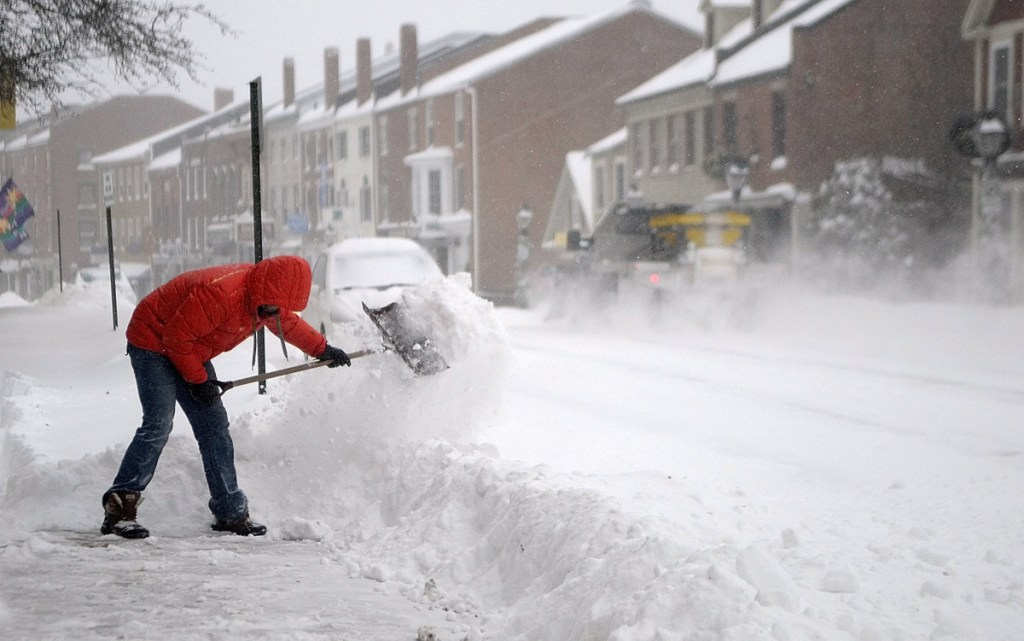 Nathan Sennett shovels snow of the sidewalk in front of Lux on Dec. 15, 2013, in Hallowell. The City Council is considering a proposed ordinance that would require downtown-area commercial property owners to clear snow from the sidewalks in front of their buildings.