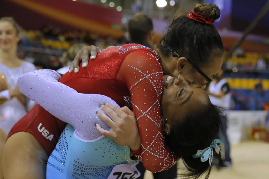 Morgan Hurd, top, a former world champion, hugs Simone Biles after Biles captured the title Thursday for the fourth time. Hurd finished third. Both are from the United States.