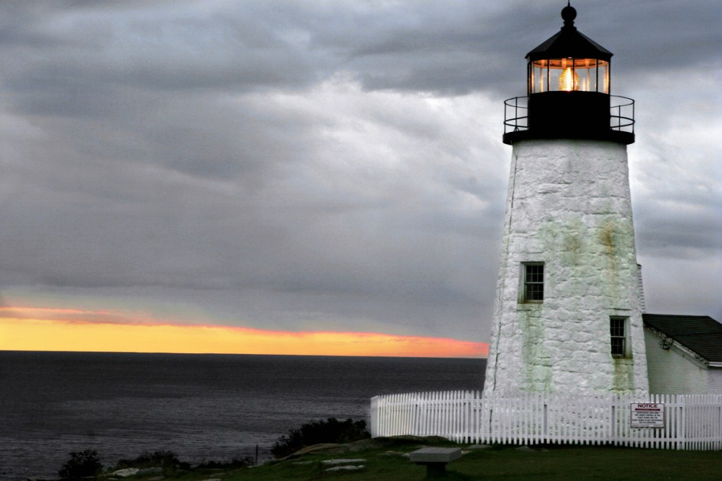 The sun sets behind a layer of clouds at Pemaquid Point Lighthouse in Bristol.