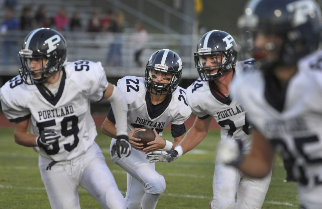 Portland quarterback Sam Knop (#22) lines up behind his blockers, #59, Ryan Howell, #24, Zach Elowitch, on a quarterback keeper play in the first quarter.  (Photo by John Ewing/Staff Photographer)