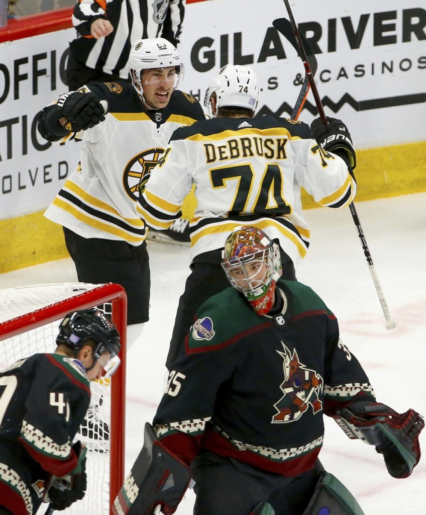 Jake DeBrusk celebrates his first-period goal with Brad Marchand during the Bruins' 2-1 win Saturday night against the Arizona Coyotes. Boston improved to 1-1-1 on a four-game road trip.